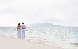 Romantic couple walking on the sea shore Stock Photos