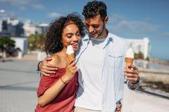 Romantic couple walking on street eating ice cream royalty free stock photography