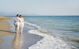 Romantic couple walking together on the beach Stock Images