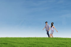 Romantic couple walking together on the meadow Stock Photos