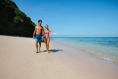 Romantic couple walking on tropical beach Stock Photos