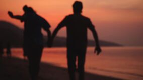Romantic couple walks on tropical beach at amazing sunset holding hands. Happy young couple enjoying travel vacation stock video