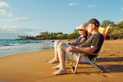 Romantic Couple Watching Sunset. Happy Romantic Couple Enjoying Beautiful Sunset at the Beach royalty free stock photography