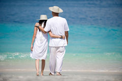 Romantic couple wearing hats on the beach Stock Photos