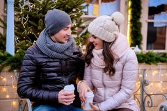 Romantic couple wearing warm clothes sitting on a bench in evening street decorated with beautiful lights, talking and. A young romantic couple wearing warm stock image