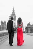 Romantic Couple on Westminster Bridge by Big Ben, London, Englan. Black and white, rear view of romantic men and women couple, the women is wearing a red dress Stock Photography