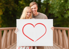 Romantic couple with white board and heart on it Stock Photos