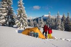 Romantic couple during the winter travel in wilderness. Men and a women are hugging next to a tent, amidst huge snow-covered fir trees and admiring the Royalty Free Stock Images