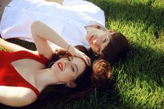 Romantic couple of young people lying on grass in park. Happy Couple Relaxing on Green Grass. Park. A girl in a beautiful dress royalty free stock photography