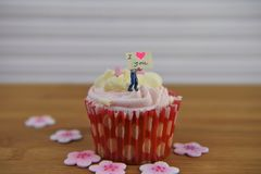 Romantic cup cake in pink and white with a miniature person figurine holding a sign board on top. Romantic cup cake with pink and white frosting in a red case Royalty Free Stock Image
