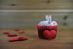 Romantic cup cake in pink and white with a miniature person figurine holding a sign board on top and red love hearts. Romantic cup cake with pink and white Stock Photo