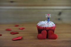 Romantic cup cake in red and white with a miniature person figurine holding a sign board on top and red love hearts. Romantic cup cake with red and white Royalty Free Stock Images