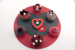 Romantic Cup Cakes. Six romantic rose red cakes on a red disc with a black and red heart Royalty Free Stock Photos
