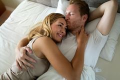 Romantic couple in bed. Romantic cute couple in bed being intimate stock image
