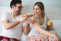 Couple eats breakfast in bed. Romantic cute couple eats breakfast in bed stock photo