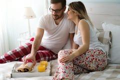 Couple eats breakfast in bed. Romantic cute couple eats breakfast in bed royalty free stock image