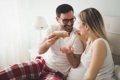 Couple eats breakfast in bed. Romantic cute couple eats breakfast in bed royalty free stock photo