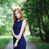 Romantic cute redhead girl in a blue dress with a forest park background Stock Photos
