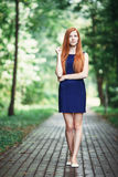 Romantic cute redhead girl in a blue dress with a forest park background. Romantic cute redhead lady in a blue dress with a forest park background stock images