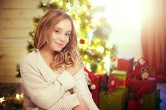 Romantic cute woman in a warm holiday sweater sitting near christmas tree. Romantic cute woman in a warm holiday sweater sitting on floor near christmas tree stock photos