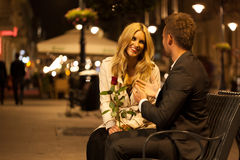 Romantic date on a bench. A men and his beutiful date talking on a bench in the evening Stock Photo