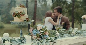 Romantic date composition: tasty cake and bouquet of flowers at the table decorated with leaves and candles at the stock footage