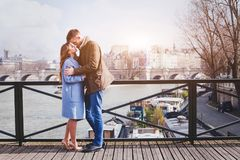 Romantic dating, young couple kissing on the bridge in Paris stock images