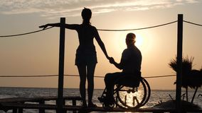 Romantic date of female with male invalid on wheelchair on jetty near sea against summer sunset. Romantic date of female with male invalid on wheelchair on jetty stock video footage