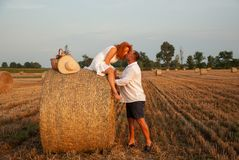 Romantic date on a freshly cut field near a haystack Stock Photography