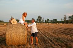 Romantic date on a freshly cut field near a haystack Stock Image