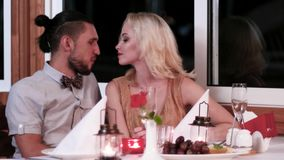 Romantic date, loving couple in the restaurant, the evening for lovers, boys and girls in a romantic atmosphere in the. Cafe, a gentle kiss, beautiful table stock video footage