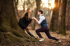 Romantic date of loving young couple in classic dress in fairytale forest park. Tic date of a loving young couple in classic dress in a fairytale forest park on stock images