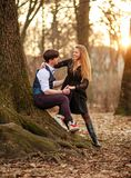 Romantic date of loving young couple in classic dress in fairytale forest park. Tic date of a loving young couple in classic dress in a fairytale forest park on stock photo