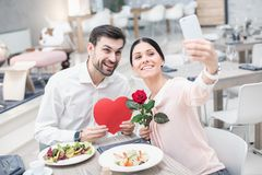 Romantic date in luxury restaurant. Date in luxury restaurant. Lovely couple in cafe with stylish interior. Man and women having delicious meal. Woman making Royalty Free Stock Photos