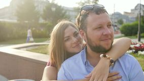 Romantic date of a young couple in the city center at sunset. Happy man and woman hug, kiss, enjoying time together stock footage