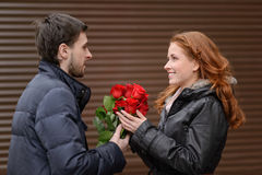 Romantic date. Young man presenting a bunch of red roses to his Royalty Free Stock Photos