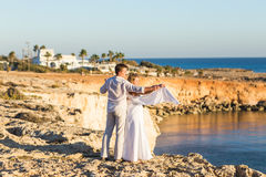 Romantic dating. Young loving couple walking together by the beach enjoying sea Royalty Free Stock Photo