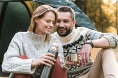Joyful man and woman drinking tea in the woods. Romantic day in the nature. Cheerful loving couple is warming up by hot beverage in the forest. Lady is holding Stock Images
