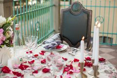 Romantic decor of the festive table in the restaurant with candles, flowers, rose petals stock images