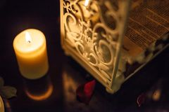 Romantic decoration, candle and white beautiful container metal wrought iron box with rose petals on the reflected black marble. Table Stock Photo