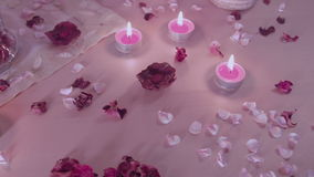 Romantic decoration, installation on a table, camera panning. Rose petals, burning candles and heart shaped pot pourri stock video footage