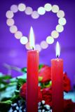 Romantic decoration for Valentine`s day concept. Bouquet of roses and candles on a ultra violet background with heart Stock Photos