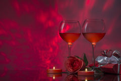 Romantic design with glasses of wine, rose, gift  and candles. Royalty Free Stock Images