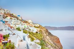 Romantic Destination. Picturesque Cityscape of Oia Village on Santorini Island with Caldera Mountains On Background in Rays of. Setting Sun. Horizontal Shot stock image