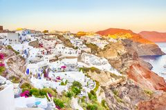 Romantic Destination. Picturesque Cityscape of Oia Village on Santorini Island with Caldera Mountains On Background in Rays of. Setting Sun. Horizontal stock photography