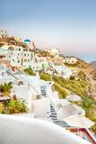 Romantic Destination. Picturesque Cityscape of Oia Village on Santorini Island with Caldera Mountains On Background. Vertical Shot royalty free stock image