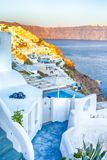Romantic Destination. Tranquil Picturesque Cityscape of Oia Village on Santorini Island with Volcanic Caldera On Background Before. Sunset.Vertical Composition stock photo