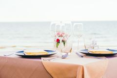 Romantic dining table setting with wine glass and other. With sea and ocean background Royalty Free Stock Photos
