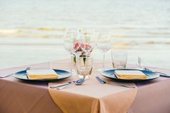 Romantic dining table setting with wine glass and other. With sea and ocean background Stock Image