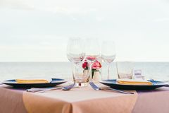 Romantic dining table setting with wine glass and other. With sea and ocean background Stock Photo